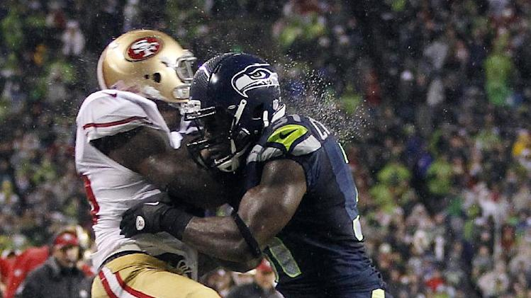 San Francisco 49ers' Vernon Davis, left, is hit by Seattle Seahawks' Kam Chancellor, right during a reception attempt in the first half of an NFL football game, Sunday, Dec. 23, 2012, in Seattle. (AP Photo/John Froschauer)