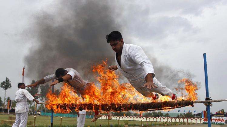 India's CRPF personnel perform a stunt during the passing out parade in Humhama, on the outskirts of Srinagar