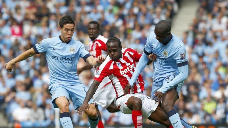Manchester City's Toure and Nasri challenge Stoke City's Moses during their English Premier League soccer match at the Etihad stadium in Manchester