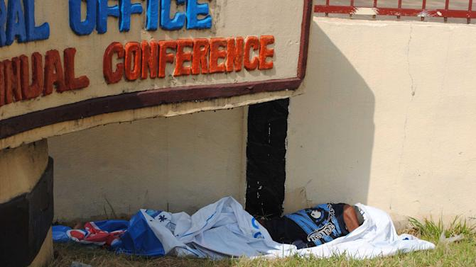 A man, suspected of suffering from symptoms of Ebola, lies in front of the United Methodist Church headquarters in Monrovia