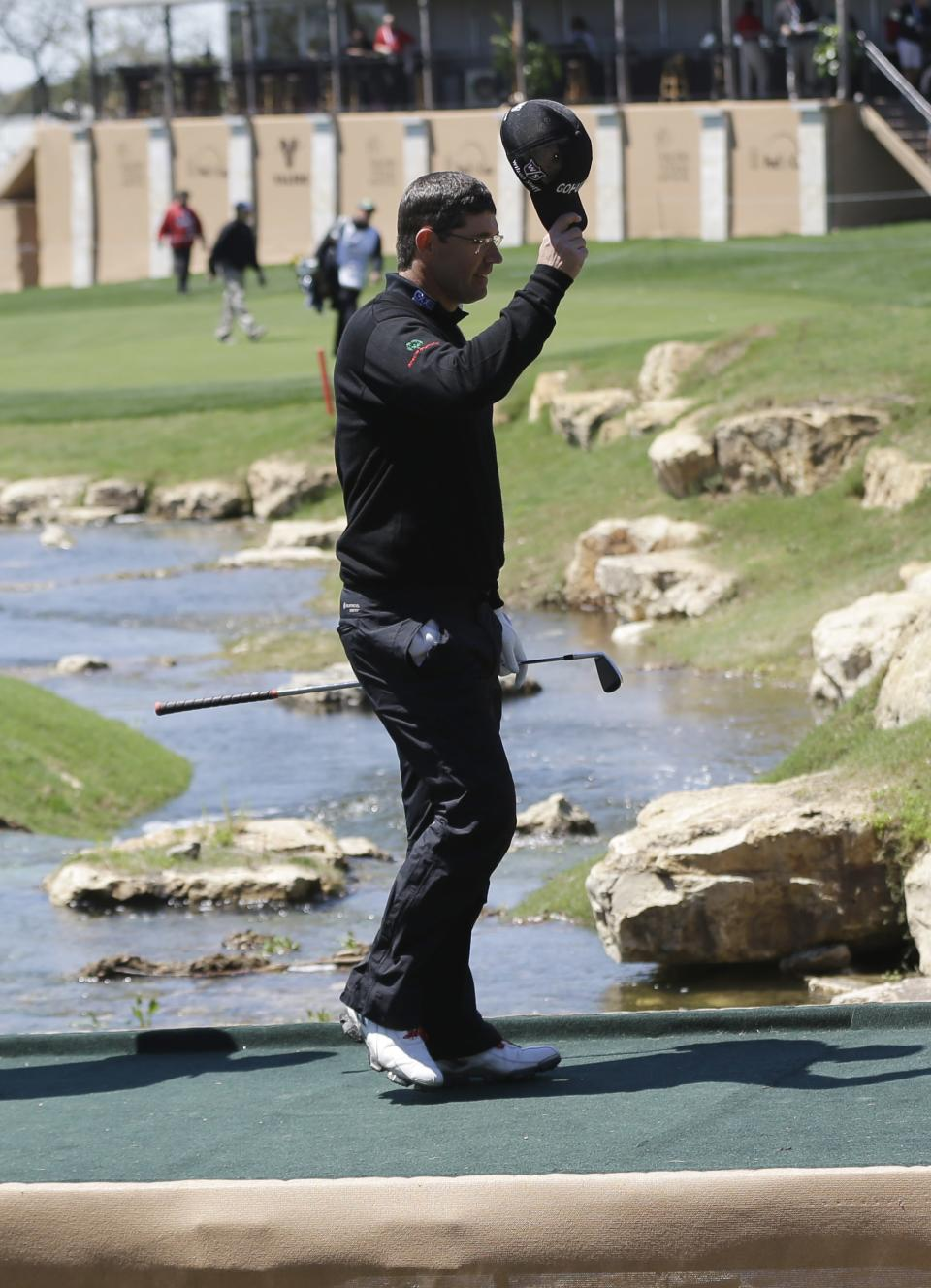Padraig Harrington, of Ireland, tips his hat to the gallery as crosses a creek the 18th hole during the first round of the Texas Open golf tournament, Thursday, April 4, 2013, in San Antonio.  (AP Photo/Eric Gay)