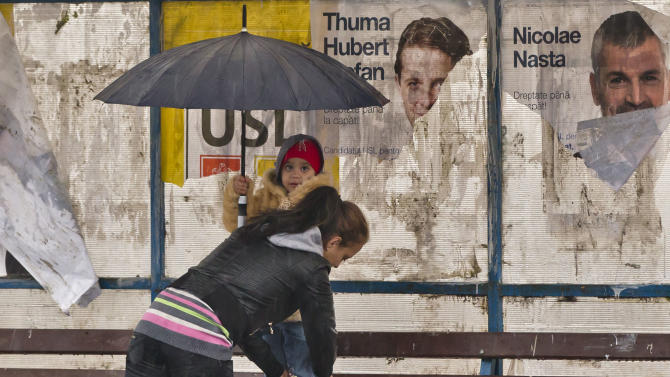 A woman and child shelter from the rain in a bus stop covered by electoral posters, on the outskirts of Bucharest, Romania, Sunday, Dec. 9, 2012. Millions of Romanians braved rain and snow Sunday as they went to the polls for a parliamentary election that center-left government is expected to win a, but the result could lead to more of the political instability that has plagued the impoverished Balkan nation this year. (AP Photo/Vadim Ghirda)