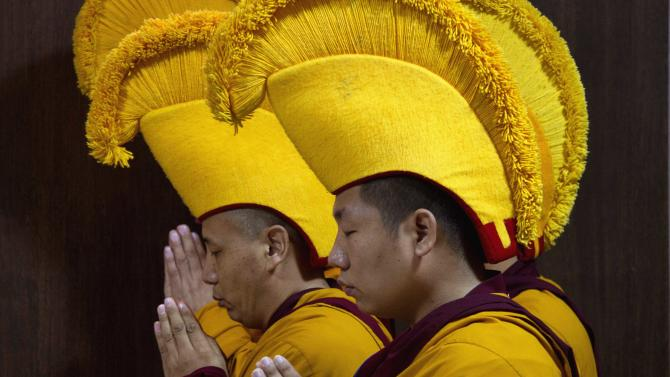 Exile Tibetan monks wearing yellow hats of the Gelug sect do ritual prayers during the opening ceremony of a meeting of the leaders of the four Tibetan Buddhist sects and pre-Buddhism Bon in Dharmsala, India, Thursday, Sept. 22, 2011. Samdhong Rinpoche, the former prime minister of the exiled government said that the leaders are likely to discuss the Dalai Lama's reincarnation among other religious issues during the three-day meet ending Saturday. (AP Photo/Ashwini Bhatia)
