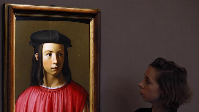 A Sotheby's employee looks at a painting, a portrait of Giovanni Gaddi (1493-1542) which is yet to find a convincing attribution, during a press viewing in London, Friday, Nov. 30, 2012. The painting estimated at 600,000-800,000 pounds (960,500-1,280,500 US Dollars) will go on sale in the evening sale of Old Master Paintings and Drawings on Dec. 5 in London. (AP Photo/Kirsty Wigglesworth)