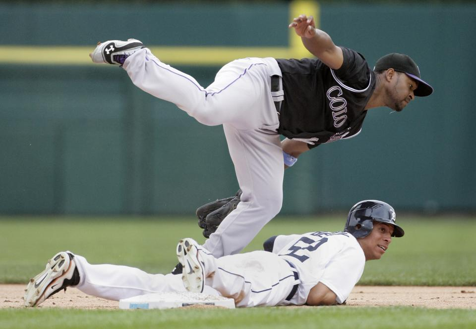 Colorado Rockies second baseman Chris Nelson, top, and Detroit Tigers' Quintin Berry watch the throw to first base to get a double play on Detroit's Miguel Cabrera in the first inning of an interleague baseball game on Sunday, June 17, 2012, in Detroit. (AP Photo/Duane Burleson)