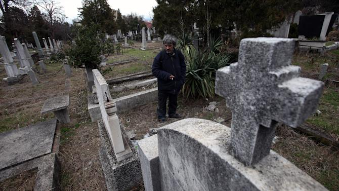 Homeless Bratislav Stojanovic walks through the cemetery near the grave where he now dwells in the city of Nis, Serbia, Thursday, Feb. 14, 2013. The 42-year-old homeless man from this southern Serbian city has been dwelling at a local cemetery for more than fifteen years, turning one of the underground tombs there into a place of his own. (AP Photo/Darko Vojinovic)