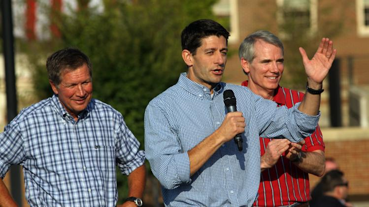 Vice Presidential candidate Rep Paul Ryan, R-Wis., center, talks to supporters at a rally on the campus of Miami University in Oxford Ohio, Wednesday Aug. 15, 2012, as Ohio Gov. John Kasich, left, and Rep. Rob Portman, listen. (AP Photo/Tom Uhlman)
