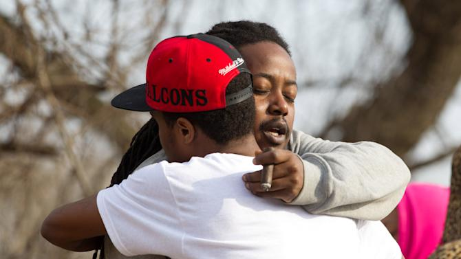 Leaman Joe, left, hugs Michael Parker, at the crash site that killed their friends on Park Ave. in Warren, Ohio on Sunday, March 10, 2013. (AP Photo/Scott R. Galvin)