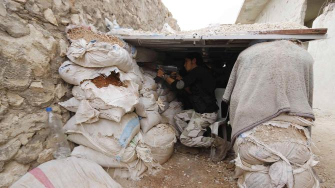 Rebel fighter takes up a position behind piles of sandbags on the Karm al-Tarab frontline in Aleppo