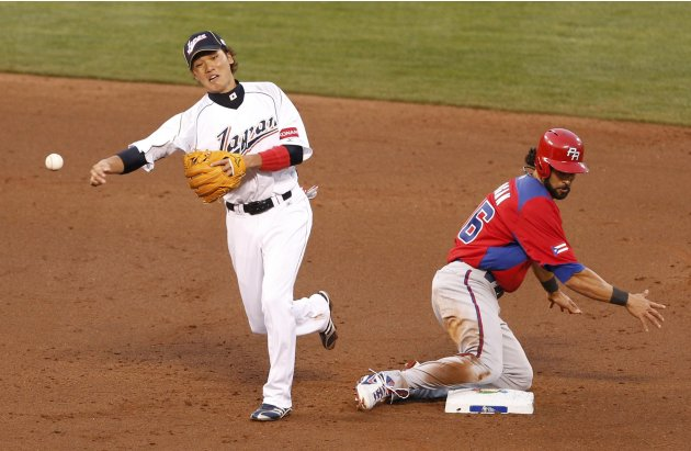 Japan's shortstop Sakamoto completes the throw to first base for the double play as Puerto Rico's Pagan slides into second base during the third inning of their semi-final World Baseball Classic game