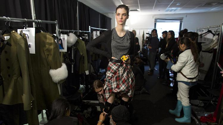A model is fitted for boots backstage before the presentation of the Prabal Gurung Fall 2013 fashion collection during Fashion Week, Saturday, Feb. 9, 2013, in New York. (AP Photo/Craig Ruttle)