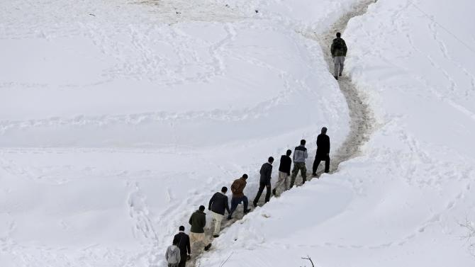Afghan survivors of an avalanche walk in the Abdullah Khil village of the Dara district of Panjshir province