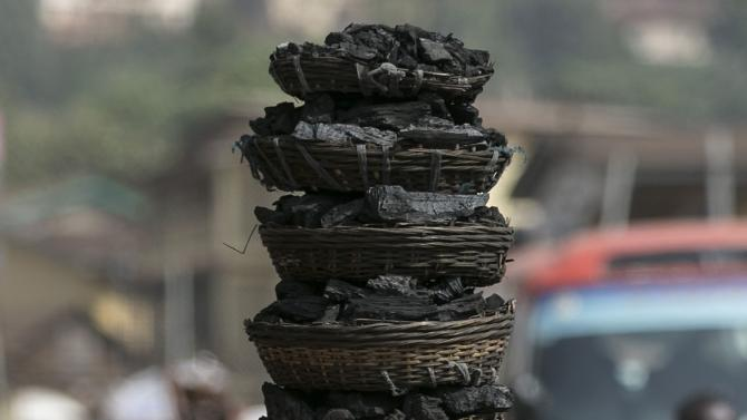 A woman carries coal baskets on her head in Freetown