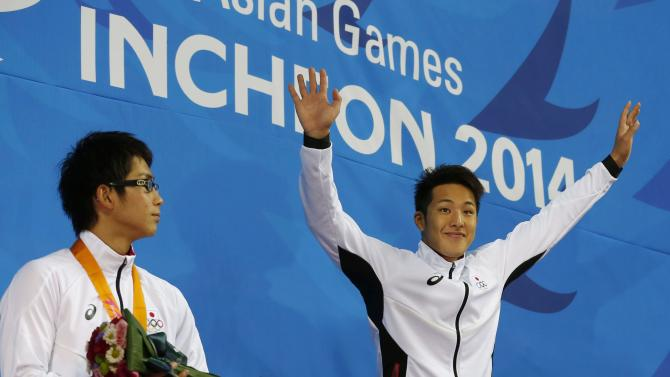 Gold medallist of Japan's Daiya Seto raises his hands next to his compatriot silver medallist Kenta Hirai after the men's 200m butterfly final swimming competition at the Munhak Park Tae-hwan Aquatics Center during the 17th Asian Games in Incheon