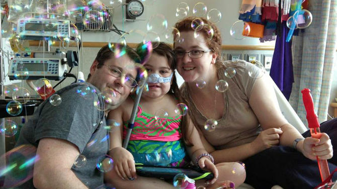 In this May 30, 2013 photo provided by the Murnaghan family, Sarah Murnaghan, center, celebrates the 100th day of her stay in Children's Hospital of Philadelphia with her father, Fran, left, and mother, Janet. Hoping to get a lung transplant, the 10-year-old suburban Philadelphia girl has been hospitalized at Children's Hospital of Philadelphia for three months with end-stage cystic fibrosis. (AP Photo/Murnaghan Family)
