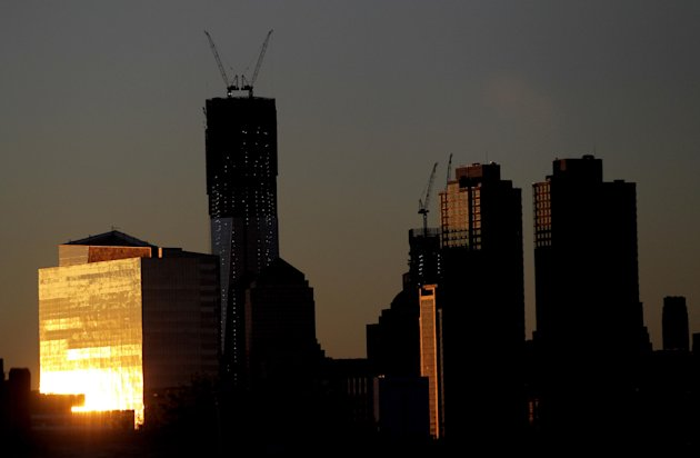 The sun reflects on a building as it rises Monday April 30, 2012, including One World Trade Center, center left, in New York as seen from Jersey City, N.J. One World Trade Center, the giant monolith being built to replace the twin towers destroyed in the Sept. 11 attacks, will lay claim to the title of New York City's tallest skyscraper on Monday. (AP Photo/Julio Cortez)