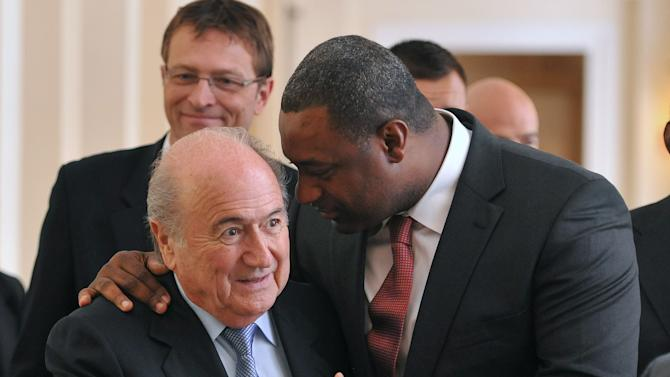 The newly elected president of CONCACAF Jeffrey Webb talks to FIFA President Joseph Blatter, left, as they arrive at the meeting of the Confederation of North, Central American and Caribbean Association Football (CONCACAF), prior to the two-day congress of FIFA in Budapest, Hungary, Wednesday, May 23, 2012. (AP Photo/MTI, Szilard Koszticsak)