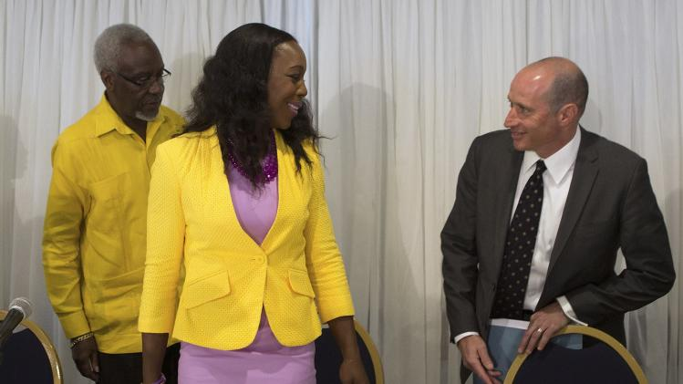 Jamaica's Veronica Campbell-Brown takes a seat between her lawyers at a news conference in Kingston