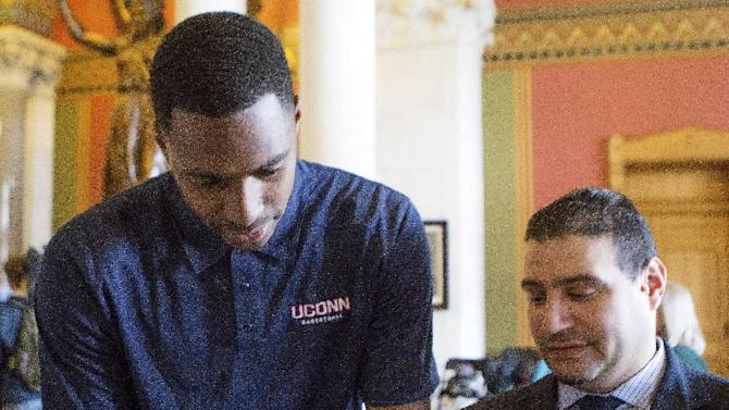 Connecticut's NCAA college basketball player Phillip Nolan, left, signs an autograph for a fan during Husky Day at the Connecticut Capitol on Wednesday, April 30, 2014, in Hartford, Conn