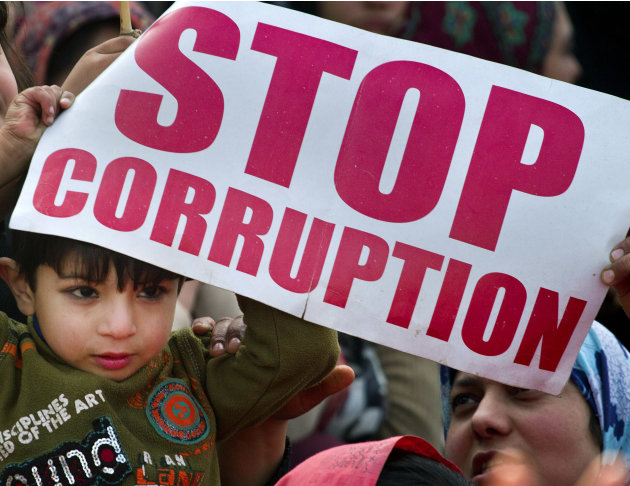 A Pakistani boy holds a placard during an anti-government rally called by Sunni Muslim cleric Tahir-ul-Qadri in Islamabad, Pakistan, Wednesday, Jan. 16, 2013. Pakistan's leaders received a powerful on