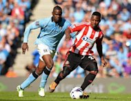 Sunderland's midfielder Stephane Sessegnon (R) clashes with Manchester City's striker Mario Balotelli during their English Premier League football match at The Etihad stadium in Manchester, north-west England. Manchester City attempted to downplay talk of another rift with their controversial forward Balotelli