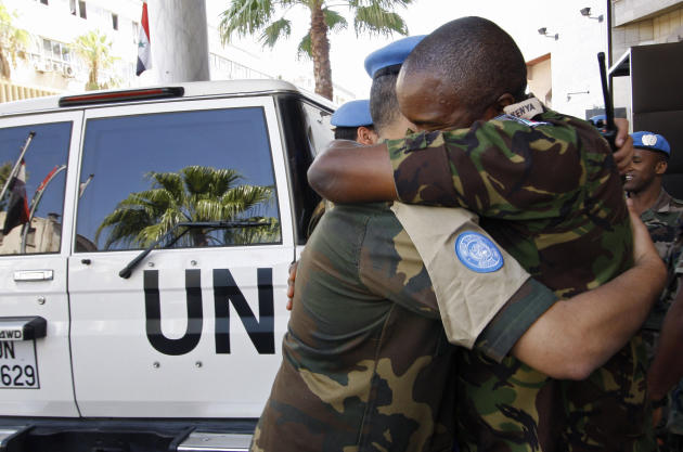 United Nations observers embrace upon arrival in Damascus, Syria from Homs, as they prepare to depart the country, Monday, Aug. 20, 2012.  Intense fighting on Monday between rebels and Syrian regime f