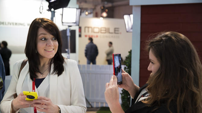 FILE - In this Tuesday, Feb. 25, 2014 file photo, a woman takes a picture with a Nokia Lumia 1520 phone as her friend smiles at the Mobile World Congress in Barcelona, Spain. The global wireless show that wraps in Barcelona on Thursday showed smartphone makers using software trickery to offset their camera weaknesses: inferior image sensors and lack of optical zoom lens. The companies are also making manipulating photos on the phone easier to learn than manually controlling DSLR cameras. (AP Photo/Marce Martinez, File)