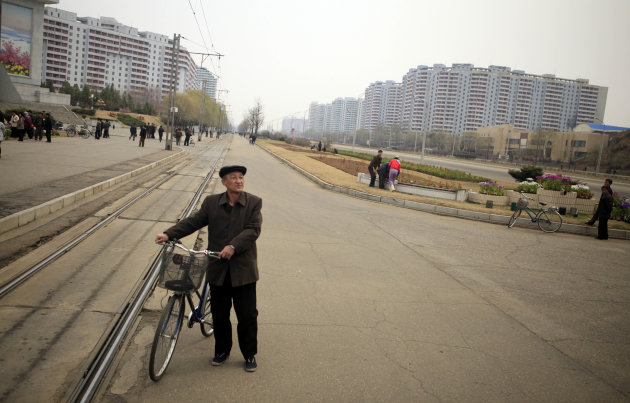 A North Korean man with his bicycle near the residential projects in Pyongyang, North Korea, on Thursday April 12, 2012. (AP Photo/Ng Han Guan)