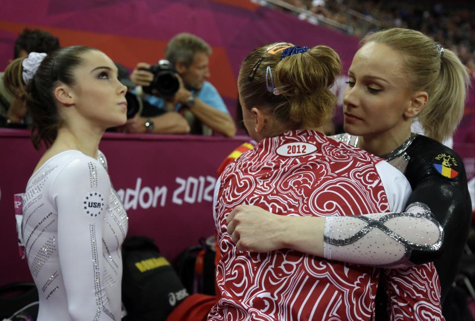 Romania's gymnast Sandra Raluca Izbasa, right, hugs Russian gymnast Maria Paseka as U.S. gymnast McKayla Maroney, left, looks at the scoreboard during the artistic gymnastics women's vault finals at the 2012 Summer Olympics, Sunday, Aug. 5, 2012, in London. (AP Photo/Julie Jacobson)