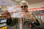 "Rolling Stones fan who named himself Patrice, 55, and who claims he has seen 54 Rolling Stones concerts, shows the tickets he bought for Thursday night's concert in Paris, Thursday, Oct. 25, 2012. The Rolling Stones announced a surprise ""warm-up gig"" in Paris, and within an hour the Champs Elysees was swarming with fans hoping to get satisfaction with one of the 350 tickets for the Thursday night show. (AP Photo/Francois Mori)"