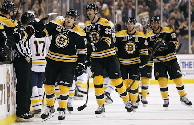 After scoring a goal, Boston Bruins' Milan Lucic leads teammates Zdeno Chara (33), David Krejci and Jarome Iginla (12) to the bench for congratulations during the third period of their 4-1 win ove