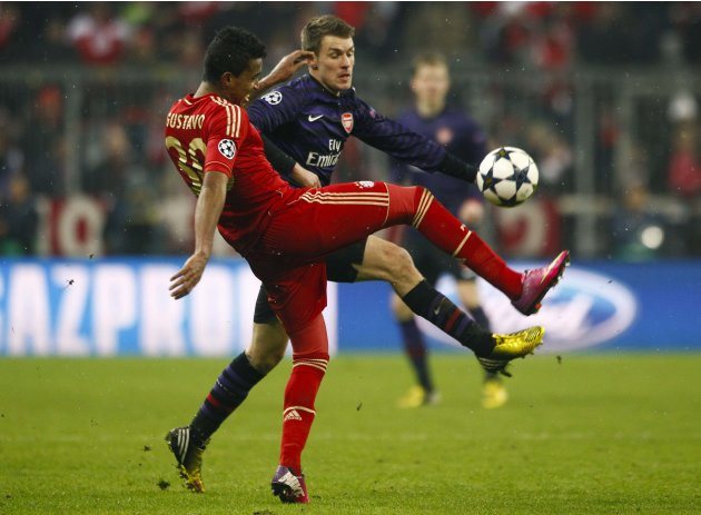Bayern Munich's Gustavo is tackled by Arsenal's  Ramsey during their Champions League round of 16 second leg match in Munich