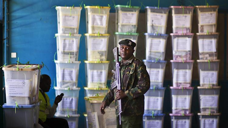 An officer of the prisons service helps to carry ballot boxes for stacking after their results were tallied, at a vote tallying center in Nairobi, Kenya Tuesday, March 5, 2013. With about a third of ballots counted provisional results showed Deputy Prime Minister Uhuru Kenyatta, who faces charges at the International Criminal Court, taking an early lead Tuesday as votes were counted the day after the country's presidential election. (AP Photo/Ben Curtis)