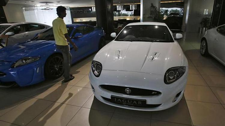 A showroom attendant walks past a Jaguar car at a Jaguar Land Rover showroom in Mumbai February 13, 2013. REUTERS/Vivek Prakash/Files