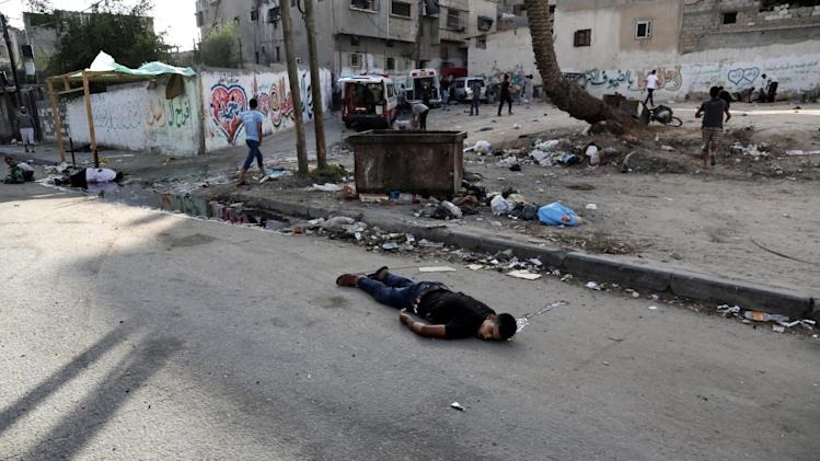 Palestinians lay on the ground following an Israeli Strike in Shijaiyah neighborhood, eastern Gaza City, Wednesday, July 30, 2014. (AP Photo/Adel Hana)