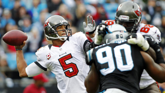 Tampa Bay Buccaneers quarterback Josh Freeman (5) throws a pass under pressure from Carolina Panthers' Frank Alexander (90) during the first half of an NFL football game in Charlotte, N.C., Sunday, Nov. 18, 2012. (AP Photo/Bob Leverone)