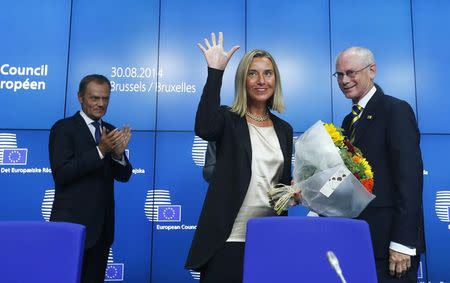 Newly elected European Council President Tusk applauds during a news conference with outgoing European Council President Van Rompuy and newly elected European High Representative for Foreign Affairs Mogherini in Brussels