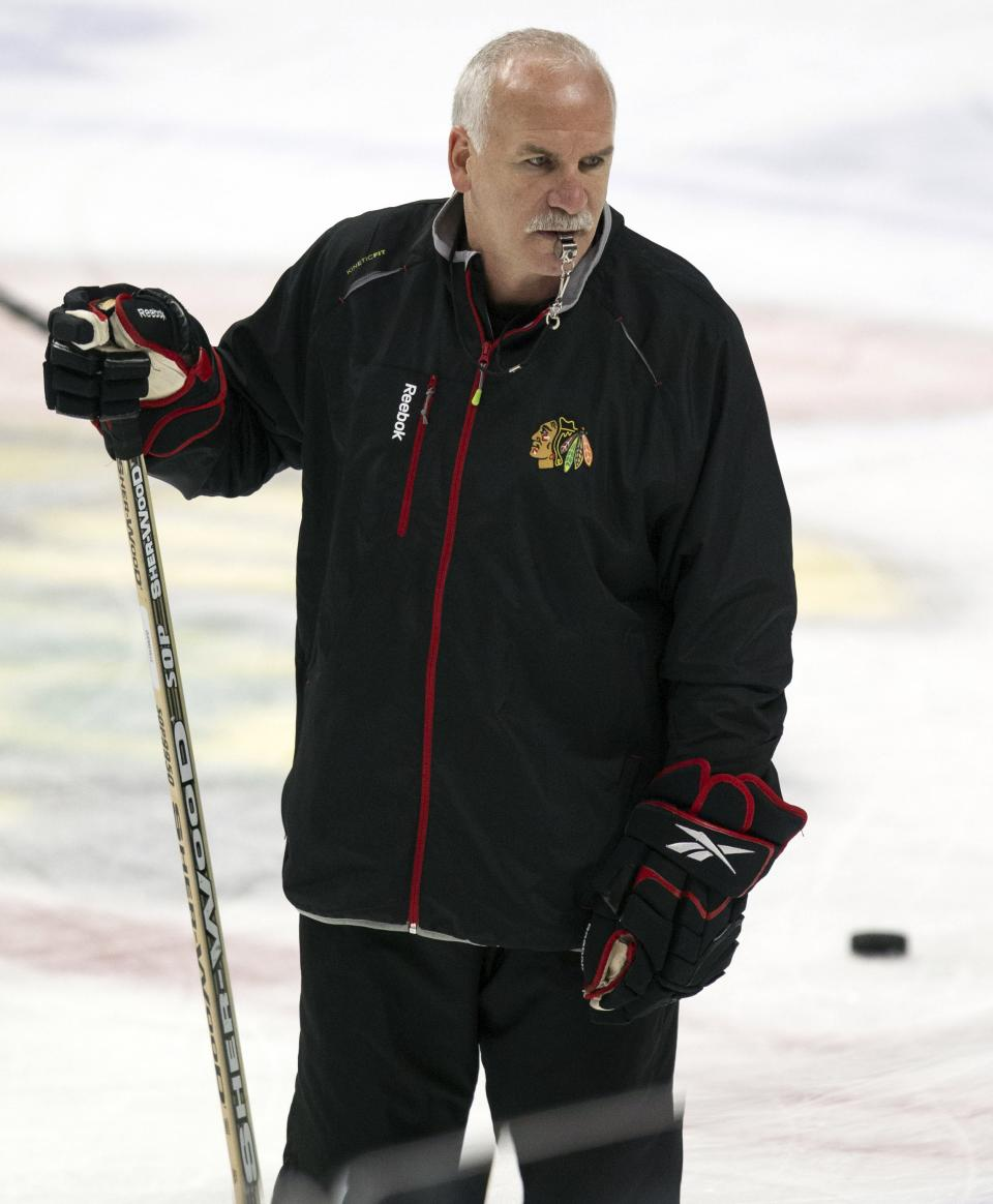 Chicago Blackhawks head coach Joel Quenneville watches as his players run a drill during NHL hockey practice Friday, June 14, 2013, in Chicago. The Blackhawks lead the Boston Bruins 1-0 in the best-of-seven games Stanley Cup final series. Game 2 is scheduled for Saturday in Chicago.  (AP Photo/Scott Eisen)