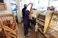 A woman buys a baguette at Sebastian Maugieux's bakery in Paris. Shops in the small central French city of Puy-en-Velay are about to launch a shared Internet site to compete with regional big box retailers, the town hall announced on Tuesday