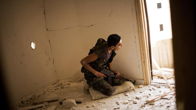 A Free Syrian Army fighter takes cover within the confines of a damaged building during clashes with the Syrian Army in Karmal Jabl district, Aleppo, Syria, Sunday, Oct. 21, 2012. (AP Photo/Manu Brabo)