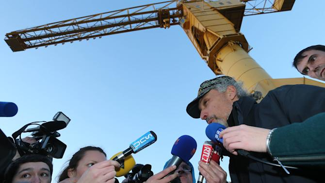 "French father Serge Charnay answers journalists after he climbed down from  the crane where he was spending the fourth day in protest, Monday, Feb,18, 2013. The man, wants France to strengthen its law on shared custody. He was convicted of taking his son on an unauthorized vacation for two months in 2011, and said he regretted nothing because ""if I hadn't I wouldn't have seen him."" (AP Photo/David Vincent)"