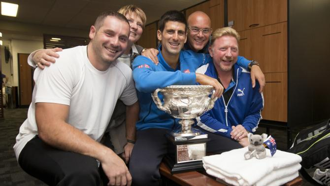 Djokovic of Serbia poses with his coach Becker, members of his support team and the men's singles trophy in the player's locker room after he defeated Murray of Britain at Australian Open tennis tournament