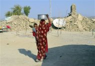 A survivor of an earthquake carries a pot on her head filled with drinking water as she walks near the rubble of a mud house after it collapsed following the quake at Dhallbedi Peernder village in Awaran district, southwestern Pakistani province of Baluchistan, September 27, 2013. REUTERS/Naseer Ahmed