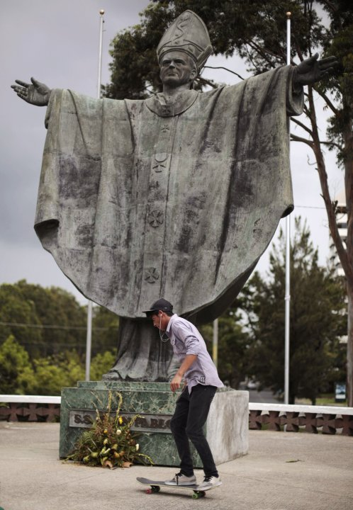 A man practises on his skateboard in front of a statue of Pope John Paul II on Go Skateboarding Day in Guatemala City