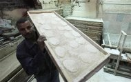 A man carries a tray of dough to be placed in an oven at a bakery in Cairo March 12, 2013. The Egyptian pound has lost more than 8 percent of its value against the U.S. dollar since the end of December as concern deepens about the state of the economy, which is being undermined by political instability and rioting. Annual consumer inflation in Egyptian cities leapt to 8.2 percent in February from 6.3 percent in January, reaching the highest level since May last year. Food and drink prices rose 9.3 percent year-on-year last month. Picture taken March 12, 2013. To match Feature EGYPT-FOOD/ REUTERS/Mohamed Abd El Ghany