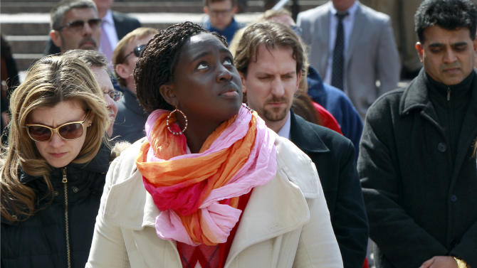 Audrey Gasteier, left, of Cambridge, Mass., and Aminata Ndiaye, center, of Boston, join others to observe a minute of silence at City Hall Plaza in Boston for the victims of the Boston Marathon bombings Monday, April 22, 2013, one week after the explosions. The remembrance was held at 2:50 p.m., the time the first of the two bombs exploded near the race's finish line. (AP Photo/Bill Sikes)