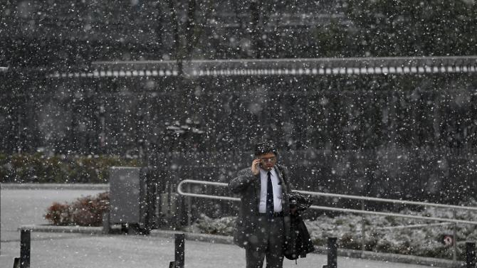 A man using a mobile phone stands on a street as snow falls in Tokyo