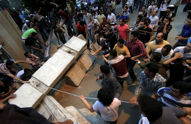 Egyptian protesters remove concrete blocks used to close the way to the Israeli embassy building as they protest on the death of Egyptian security forces by the Israelis in Sinai, in Cairo, Egypt, Sat