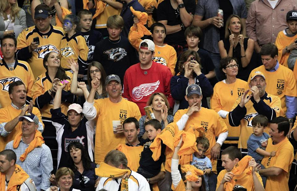 A Detroit Red Wings fan, center, is surrounded by celebrating Nashville Predators fans as the Predators defeated the Red Wings 2-1 in Game 5 of a first-round NHL hockey playoff series on Friday, April 20, 2012, in Nashville, Tenn. The Predators won the series 4-1. (AP Photo/Mark Humphrey)