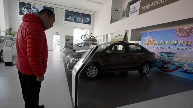 A customer looks at a Peugeot car on display at a Dongfeng and Peugeot joint venture show room in Beijing Wednesday, Feb. 19, 2014. Loss-making French carmaker PSA Peugeot Citroen is getting a 3 billion euro lifeline backed by Chinese investors and the French government in a deal that will see the company's founding family hand over control after more than two centuries at the helm. Chinese automaker Dongfeng and the French government are each investing 800 million euros ($1.1 billion) in Peugeot, throwing a financial lifeline to the struggling French auto brand and possibly expanding its global presence. (AP Photo/Ng Han Guan)